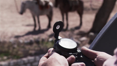 Man looking at a compass, a couple of horses look, behind Live Action