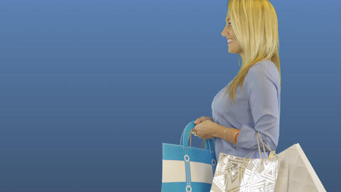 Happy young woman shopaholic with shopping bags walks. Side view profile Footage