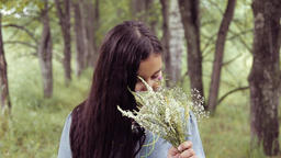Portrait. A sweet beautiful little girl is sniffing a bouquet of flowers Footage