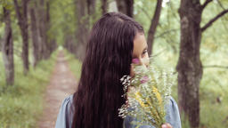 Portrait. A sweet beautiful little girl sniffs a bouquet of flowers standing on Footage