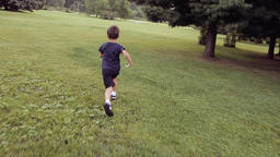 A little boy runs quickly across the grass falling and lying in a happy mood Footage