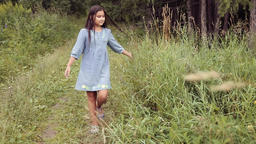 A Little beautiful girl is walking along the path in the forest and smiling Footage