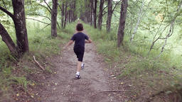 A happy beautiful little boy running through the park jumping and smiling in a Footage