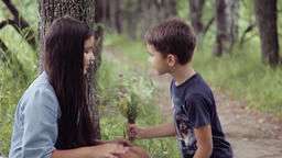 Portrait. A little boy gives a little girl flowers kissing her and hugging her Footage