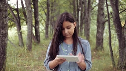 Portrait. A Beautiful girl is walking in nature using a tablet ビデオ