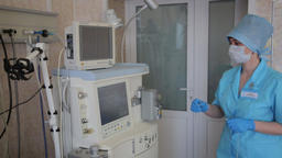 A female nurse prepares an electronic innovative medical device for surgical Footage