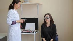 Woman doctor examines a woman's vision to a patient using new medical Footage