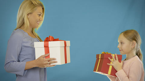 Mom and daughter give gifts to each other. Mom gives the daughter a gift box. My Live Action