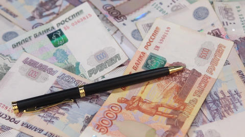 Rotation pen, lying on the background of rubles Footage