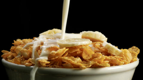 Milk pouring into bowl of cornflakes cereal and bananas Footage