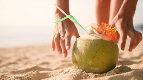 Young Tourist Girl Pick Up Delicious Fresh Thai Coconut Cocktail from Sand after Live Action