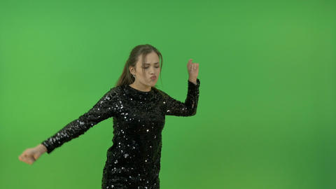 A young girl in a black shiny dress, dancing and singing. Cheerfully jumps and Footage