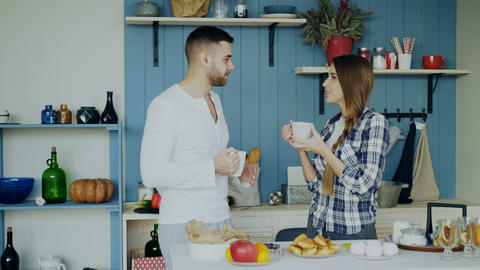 Attractive couple talking and drinking coffee in the kitchen in the morning at Footage