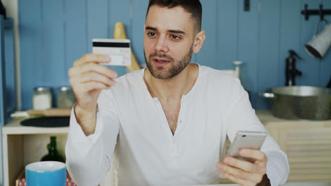 Young man having online shopping using credit card and smartphone while have Footage
