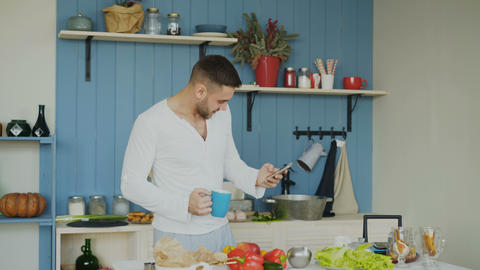 Cheerful happy man dancing and singing in kitchen while surfing social media on Footage
