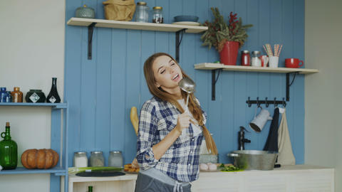 Cheerful young funny woman dancing and singing with ladle while having leisure Footage