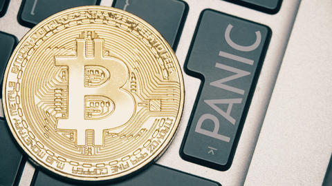 Shiny bitcoin on the computer keyboard and the PANIC button being pressed Live Action