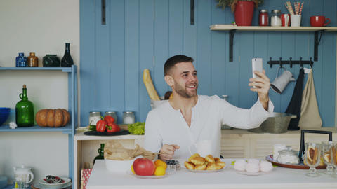 Cheerful young man using smartphone for online video chat with girlfriend while Footage