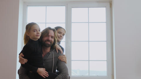Man squats with little daughters in hands Footage