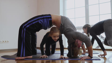 Father makes a bridge pose and daughters crawls under him Footage