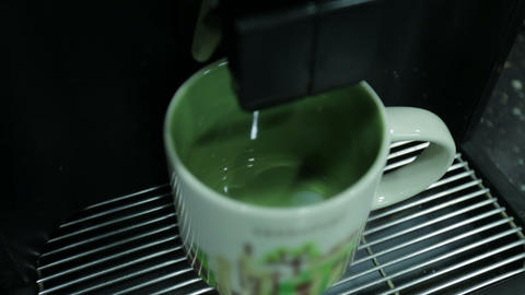 Сoffee machine pours coffee latte into a сup. Close up Image