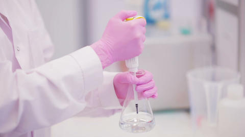 Biotechnologist takes a sample of liquid to test Footage