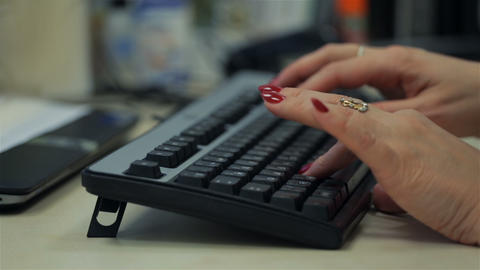 Adult woman typing on black keyboard. Close up Footage