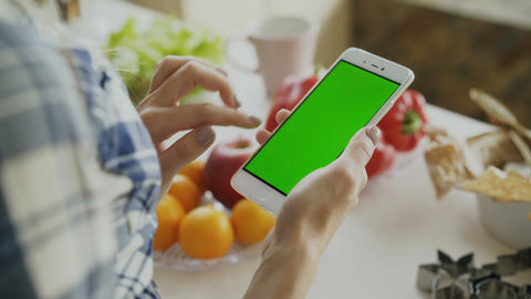 Closeup of woman's hand browsing smartphone with green screen on kitchen at home Footage