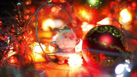 A small silver figure of Santa Claus stands near a red Christmas Hanging Bauble Footage