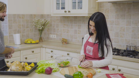 Housewife preparing the salad and talks with her husband at the kitchen Footage