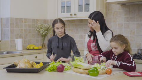 Daughters helps their mother to cook salad Footage