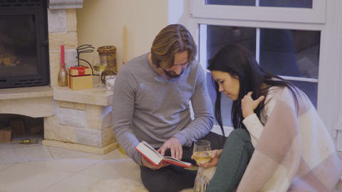 Happy married couple read book relaxing near fireplace Footage