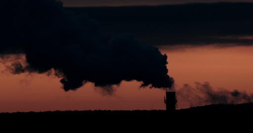 Silhouette of smoke from the chimney against the sky before sunrise. Telephoto Footage