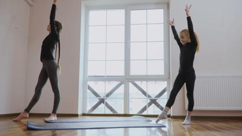 Two girls makes a bridge poses showing their flexibility and stretching Live Action