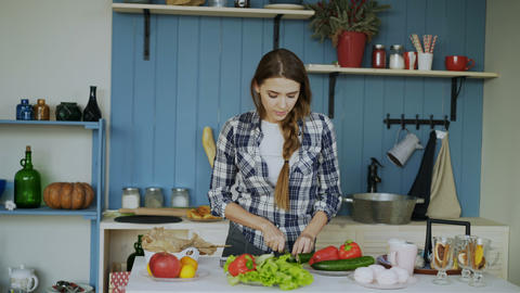 Cheerful young funny woman dancing and singing while cooking breakfast in the Footage