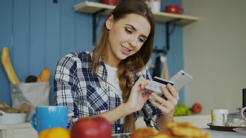 Cheerful woman paying bills online using smartphone and credit card while have Footage