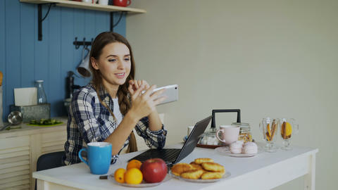 Cheerful smiling woamn talking online video chat using smartphone in the kitchen Footage