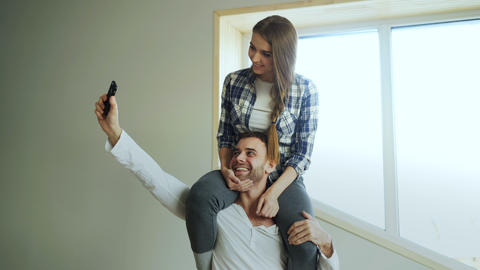 Happy young couple having fun in kitchen at home. Girl is sitting on boyfriend's Footage