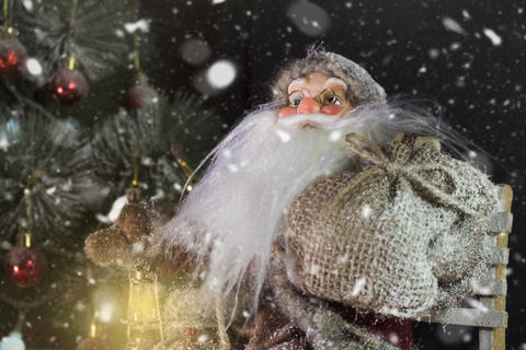 Santa Claus Outdoors Beside Christmas Tree in Snowfall Carrying Gifts to Fotografía
