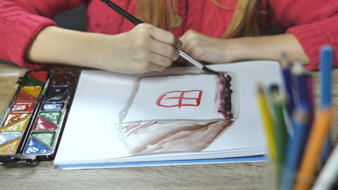 Child's hands drawing a house with paintbrush Bild