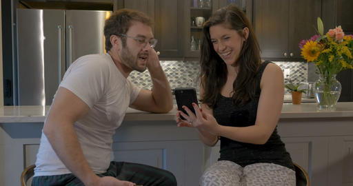 Beautiful couple talking and having fun with their smart phone technology apps Footage