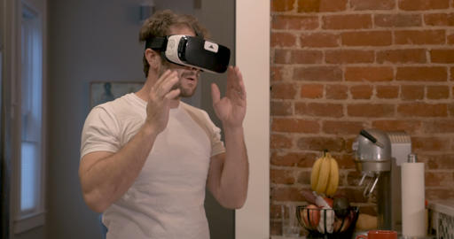 Handsome young millennial male starting his day putting on virtual reality head Live Action