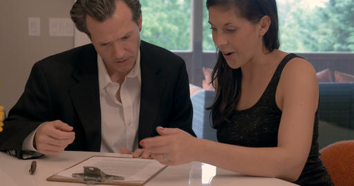 Attractive man and beautiful woman signing paperwork contract or agreement Bild