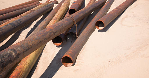 Rusty Steel Pipes Scattered in the Sand GIF