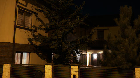 Establishing shot of residential house with lights turning on and off during Footage