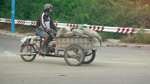 Vietnamese laborer transporting bags of cement on cargo tricycle in Nha Trang Footage