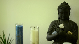Buddha - statue with candles and nature (flower) Footage