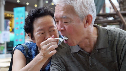 Asian senior couple eating an ice cream and feed each other abstract eternal Footage