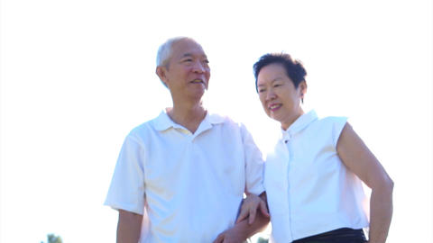 Cool Asian senior couple enjoying sunshine in nature meadow field on white shirt ビデオ
