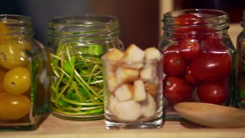 salad ingredients in jars, crispy bread, tomatoes, green vegetable Footage